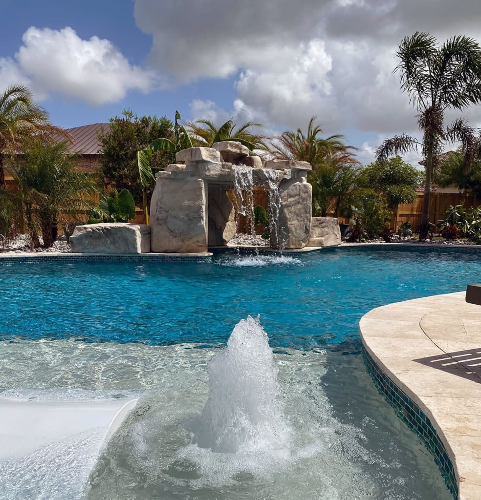 Residential swimming pool with RicoRock faux rock mini cave waterfall.