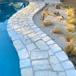 Poolside zen garden next to RicoRock faux rock coping in light shades.